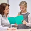 School girl with notebook and teacher in classroom — Stock Photo #63007605