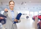 Businesswoman or saleswoman giving car key — Stock fotografie