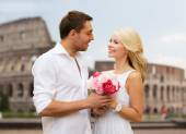 Happy couple with bunch of flowers over coliseum — Stock Photo