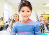 Little school girl over classroom background — Stock Photo