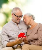 Happy senior couple with red gift box — Stock Photo
