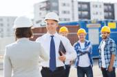 Group of smiling builders in hardhats outdoors — Stock Photo
