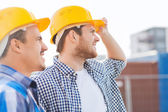Group of smiling builders in hardhats outdoors — Foto de Stock