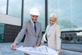 Smiling businessmen with blueprint and helmets — Stock Photo