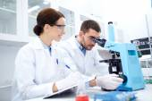 Scientists with clipboard and microscope in lab — Stock Photo