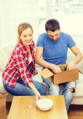 Smiling couple unpacking kitchenware — Stock Photo