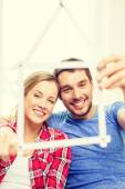 Smiling couple with house from measuring tape — Stock Photo