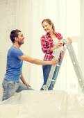 Smiling couple hanging curtains — Stock Photo