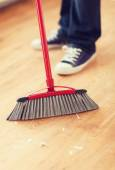 Close up of male brooming wooden floor — Stock Photo