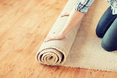 Close up of male hands unrolling carpet — Stock Photo