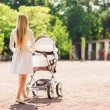 Happy mother with stroller in park — Stock Photo #63094873