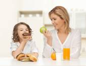 Happy mother and daughter eating breakfast — Stock Photo