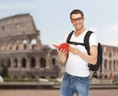Happy young man with backpack and book travelling — Foto Stock