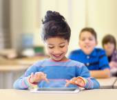 Little school girl with tablet pc over classroom — Stock Photo