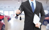Close up of businessman or salesman giving car key — Stock Photo