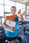 Smiling woman with scales and towel in gym — Stock Photo