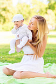 Happy mother with little baby sitting on blanket — Stock Photo