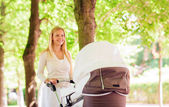 Happy mother with stroller in park — Stock Photo