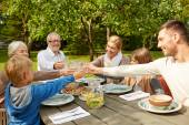 Happy family having dinner in summer garden — Stock Photo