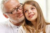 Grandfather with crying granddaughter at home — Stock Photo