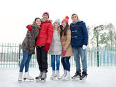 Happy friends ice skating on rink outdoors — Stock Photo