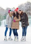 Happy young women with smartphone on skating rink — Stock Photo