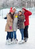 Happy friends with smartphone on ice skating rink — Stock Photo