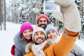 Smiling friends with camera in winter forest — Stock Photo