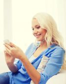 Smiling woman with smartphone at home — Stock Photo