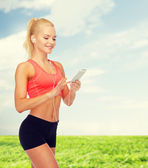 Smiling sporty woman with smartphone and earphones — Stock Photo
