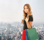 Young happy woman with shopping bags over city — Stock Photo