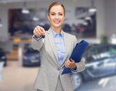 Businesswoman or saleswoman giving car key — Stockfoto