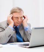 Upset older businessman with laptop in office — Stockfoto