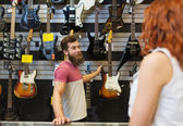 Assistant showing customer guitar at music store — Stock Photo
