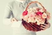 Man holding basket full of flowers and postcard — Fotografia Stock