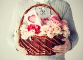 Man holding basket full of flowers and postcard — Stock Photo
