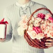 Man holding basket full of flowers and gift box — Stock Photo #63500021