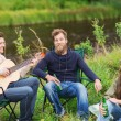 Group of tourists playing guitar in camping — Stock Photo #63509105