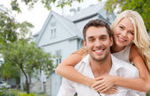 Smiling couple hugging over house background — Stock Photo