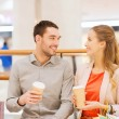 Happy couple with shopping bags drinking coffee — Stock Photo #63510783