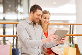 Couple with tablet pc and shopping bags in mall — Stock Photo