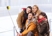 Happy friends with smartphone on skating rink — Foto de Stock