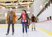 Happy friends on skating rink — Stock Photo