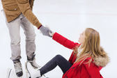 Man helping women to rise up on skating rink — Stock Photo