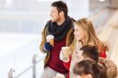 Happy friends with coffee cups on skating rink — Stock Photo