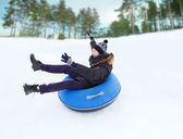 Happy young man sliding down on snow tube — Stock Photo