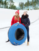 Happy girl friends with snow tubes outdoors — Stock Photo