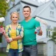 Smiling couple with paint rollers over house — Stock Photo #63594089