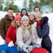 Smiling friends with snow tubes and selfie stick — Stock Photo #63598911