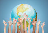 Human hands showing ok sign over earth globe — Stock Photo